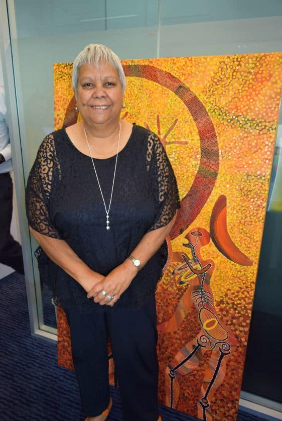Jackie Huggins, standing in front of some Indigenous artwork.