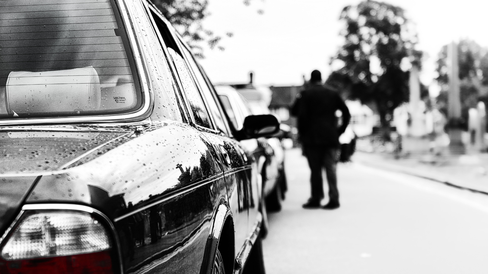 Black and white photo of a person standing next to a car