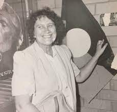 Alma Thorpe stanind in front of an Aboriginal flag.